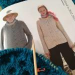 「毛糸だまvol.156」より、野呂 英作の くれよんソロ で青いアラン模様のカーディガンを編んでいます。